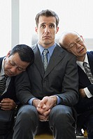 Businessmen fallen asleep on another businessman