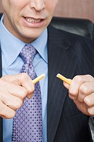 Businessman breaking pencil