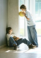 Boy sitting on floor studying, friend holding basketball, talking to him