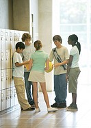 Group of teens standing in hallway near lockers