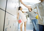 Teenage boy and girl leaning against lockers, talking