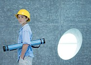 Boy holding document tube under arm and wearing hard hat