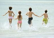 Children running in surf at beach