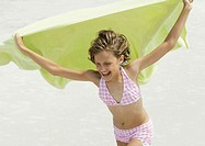 Girl holding up towel in wind, on beach