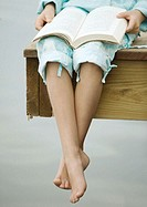 Girl sitting on edge of dock, reading book