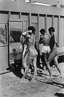 Three teenage boys flexing their muscles and posing in front of mirrors outdoors at the beach.   Image was taken in the 1950's.
