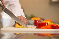 Female chef slicing peppers on chopping board, close-up