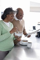 Senior couple having breakfast in kitchen, man reading newspaper, side view
