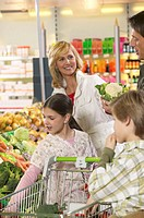 Parents and children (8-10) shopping in produce aisle of supermarket