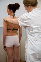 Osteopath examining female patient, rear view