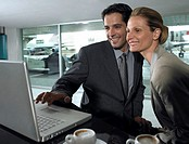 Businessman and woman using laptop computer in airport, smiling
