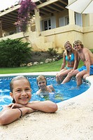 Parents and children (9-11) in outdoor pool, smiling, portrait