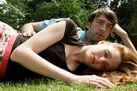 Young couple lying on grass, woman with eyes closed, close-up