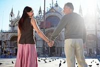 Italy, Venice, mature couple holding hands in square, rear view