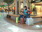 Mother sitting with two sons (4-6) in shopping centre