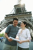 France, Paris, couple standing by Eiffel Tower, woman pointing at map