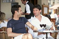 France, Paris, two men at cafe table, glasses of red wine on table