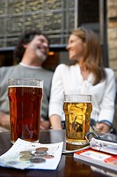 Couple outside pub, smiling, drinks and money on table in foreground