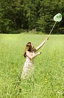 Young woman chasing butterflies in field