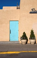 An empty sidewalk and potted trees by a closed blue door of an adobe building in Taos, New Mexico, USA