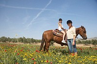 Mother standing by daughter (10-12) on horse in field, smiling