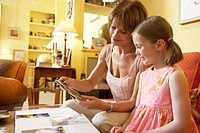 Grandmother looking at photographs with granddaughter (6-8) smiling
