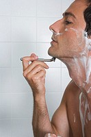Bare chested man shaving, profile