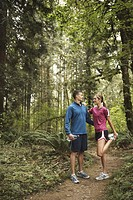 Man and woman on footpath in forest, woman stretching, side view