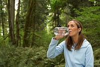 Woman drinking water in forest