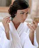 Young woman wearing dressing gown applying make-up in compact mirror