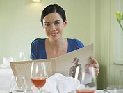 Young woman in restaurant, holding menu, smiling, portrait