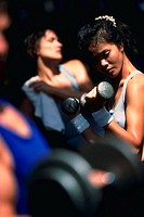 Asian woman with barbells, lifting weights while another woman stretches in background and man lifts barbell in foreground.