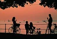 Family on bicycles silhouetted against an orange sky at dusk enjoying the view and eating ice cream.