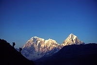 Two mountain climbers hiking along the Solo Khumbu, Nepal in twilight as the sun illuminates the Himalayan peaks behind them.