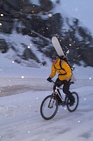 A man riding a mountain bike with a snowboard on his back during a snowstorm on Donner Pass, CA.