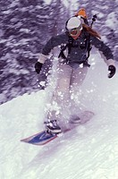 A woman snowboarding in a storm on Mount Millicent near Brighton, UT.