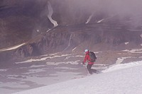 A woman skiing on a glacier above the clouds on Mount Vsesevidov in the Aleutian Islands in Alaska.