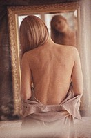 Woman looking in mirror, rear view (soft focus)