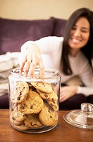 Woman putting hand into cookie jar