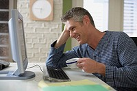 Man Enjoying Coffee While Using His Computer