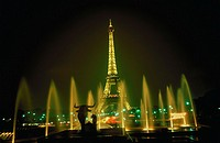 View of the Eiffel Tower in Paris, France illuminated at night with fountains in the foreground.