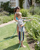 Brother and sister (6-8) watering plants in garden with hoses