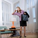 Professional Woman in Living Room Quickly Drinking Coffee (thumbnail)