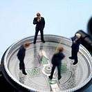 Businessmen figurines standing on compass, close up