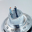 Businessmen figurines standing on dial, close up