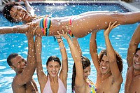 Young Woman Being Lifted by Friends in Swimming Pool