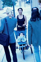 Portrait of a mother pushing her son in a baby stroller