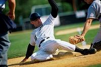 Baseball player sliding onto base