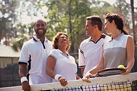 Low angle view of two mid adult couples smiling on a tennis court