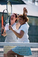 Two mid adult women cheering after winning a tennis match